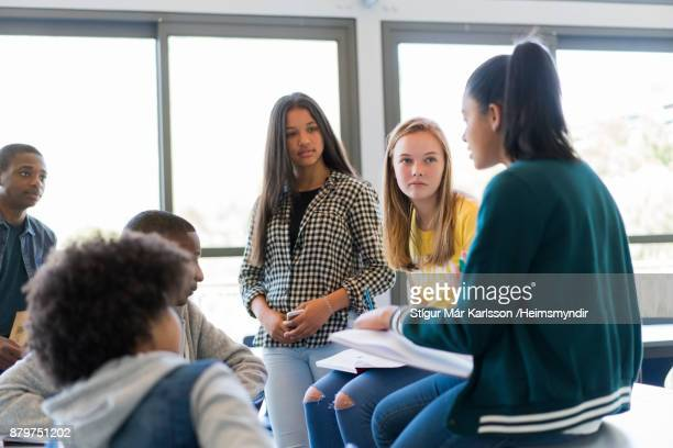 multi-ethnic students discussing in classroom - adolescente imagens e fotografias de stock
