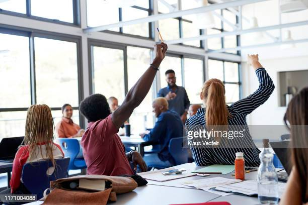 multi-ethnic students raising hands at desk - participant stock pictures, royalty-free photos & images