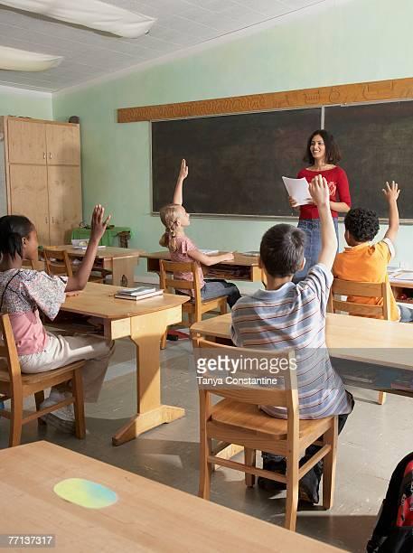 Multi-ethnic students raising hands in class