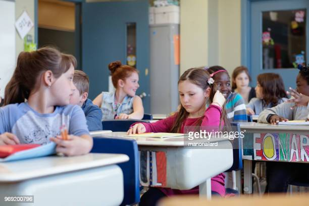 Multi-ethnic students sit into the class for the first day at school