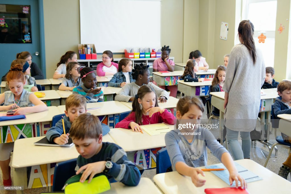 Multi-ethnic students sit into the class for the first day at school : Stock Photo