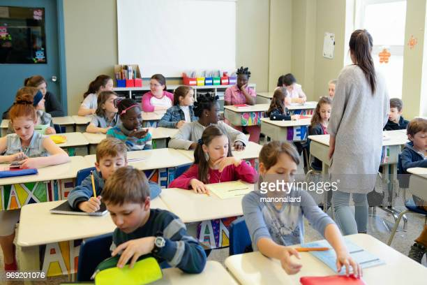 multi-ethnic students sit into the class for the first day at school - classroom stock pictures, royalty-free photos & images