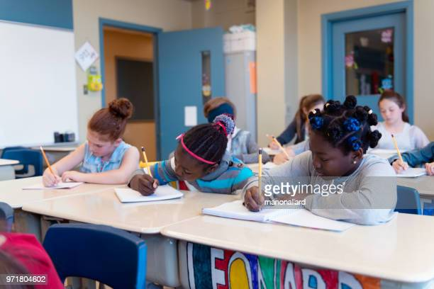 multi-ethnic students sit into the class for the first day at school - state school stock pictures, royalty-free photos & images