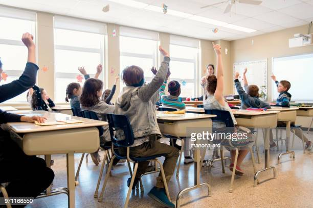 multi-ethnic students sit into the class with arms raised - primary age child stock pictures, royalty-free photos & images
