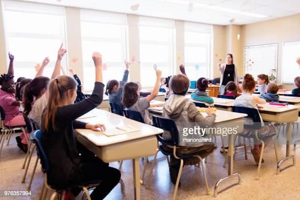 multi-ethnische studenten sitzen in der klasse mit erhobenen armen - staatliche schule stock-fotos und bilder