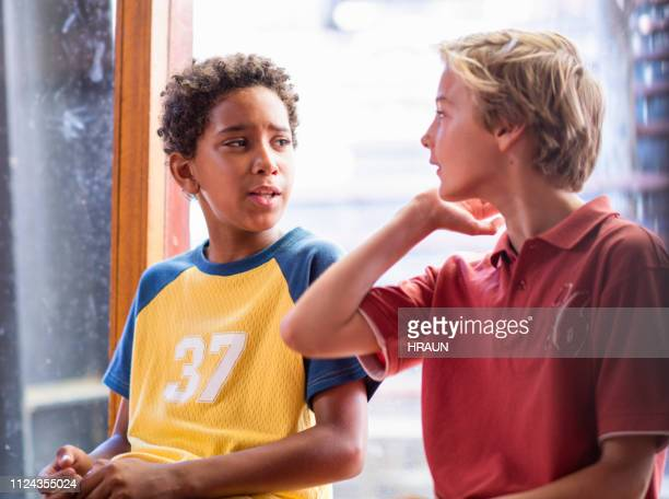 multi-ethnic students talking against window - junior level stock pictures, royalty-free photos & images