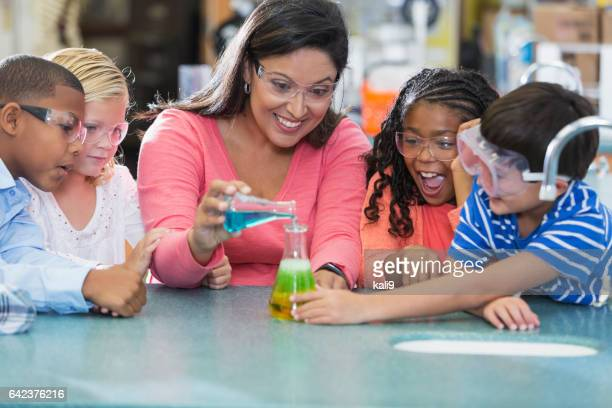 Multi-ethnic teacher and children in science lab