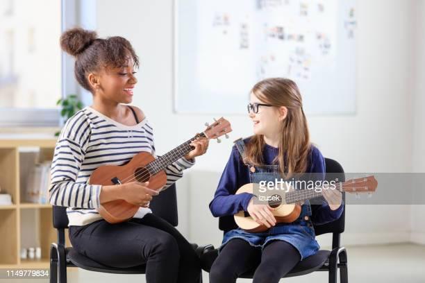 multi-ethnic teacher and student playing ukulele - ukulele stock pictures, royalty-free photos & images