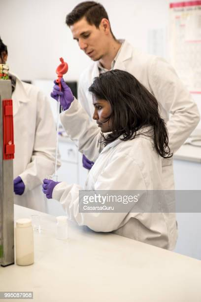 multi-ethnic team doing experiments - physicist stock pictures, royalty-free photos & images