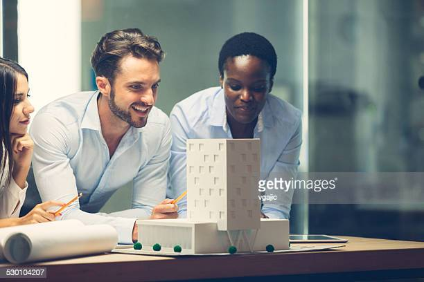 multiethnic team of architects reviewing architectural model in the office. - architectural model stock pictures, royalty-free photos & images