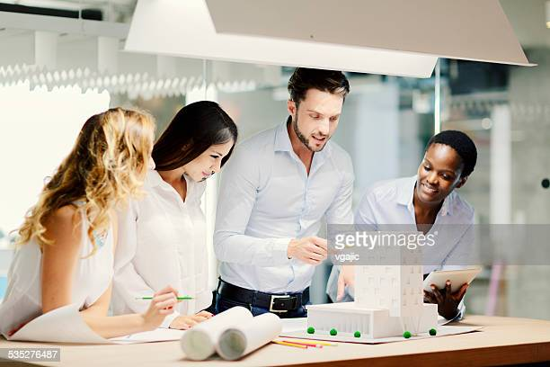 Multiethnic Team of architects reviewing architectural model in the office.