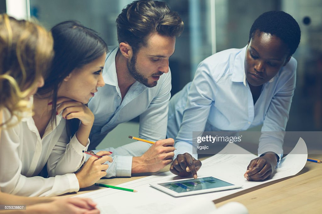 Multiethnic Team of architects reviewing reports in the office. : Stock Photo