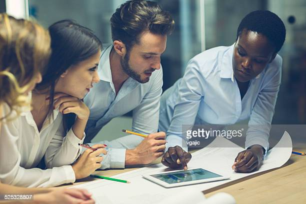 multiethnic team of architects reviewing reports in the office. - council flat stock pictures, royalty-free photos & images