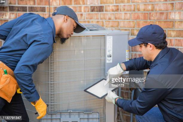 multi-ethnic team of blue collar air conditioner repairmen at work. - ventilator stock pictures, royalty-free photos & images