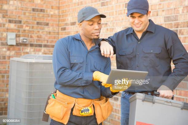 Multi-ethnic team of blue collar air conditioner repairmen at work.