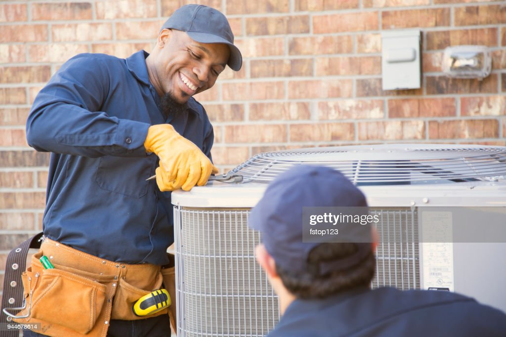 Multi-ethnic team of blue collar air conditioner repairmen at work. : Stock Photo