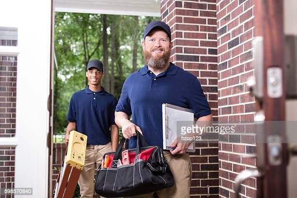 Multi-ethnic team of repairmen at customer's front door.