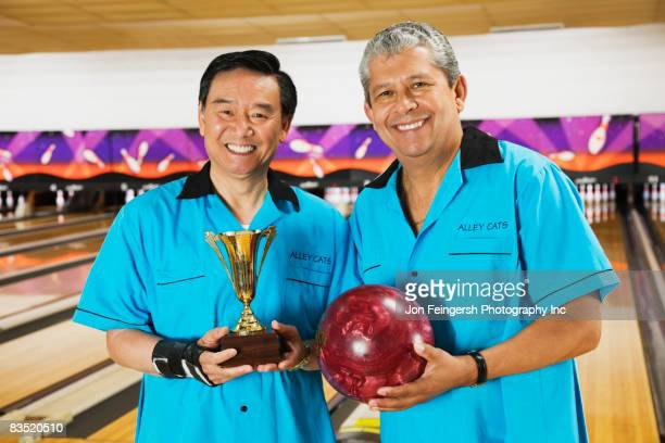 Multi-ethnic teammates holding bowling ball and trophy