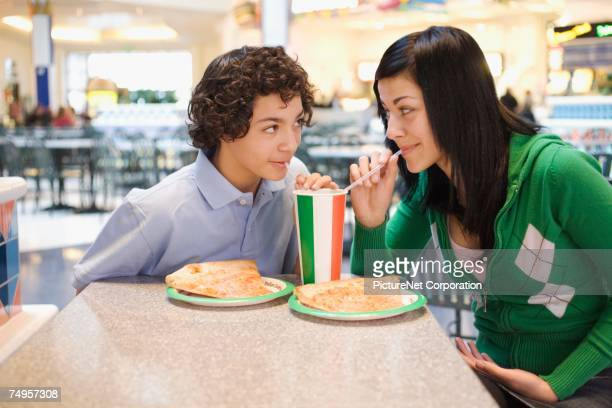 Multi-ethnic teenage couple eating at mall