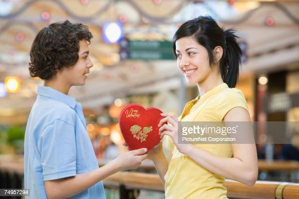 Multi-ethnic teenage couple exchanging Valentine's Day gift