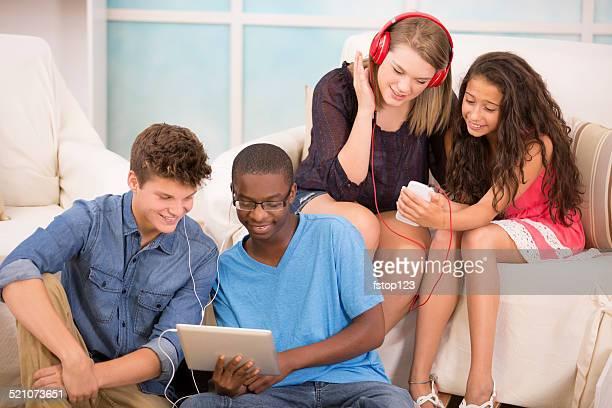 Multi-ethnischen Teenager Freunden Musik zu hören. Kopfhörer, funktioniert wie zu Hause fühlen.