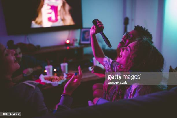 multi-ethnic teenage girls having fun singing at slumber party - party stock pictures, royalty-free photos & images