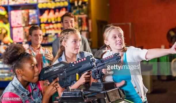 adolescentes y multiétnicas de diversión arcade - sala de máquinas recreativas fotografías e imágenes de stock