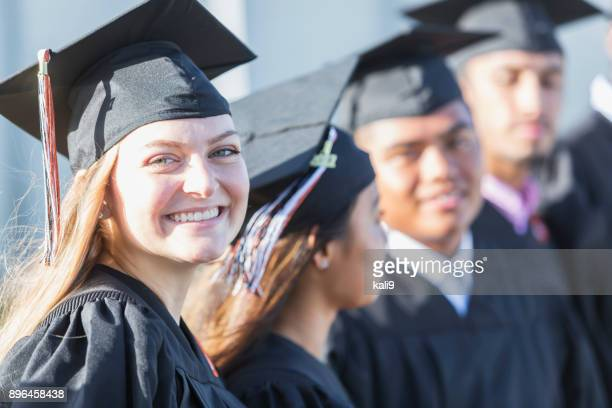 multi-ethnic teenage graduates in cap and gown - high school graduation stock pictures, royalty-free photos & images