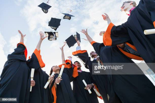 multi-ethnic teenage graduates throw caps in air - lanciare foto e immagini stock