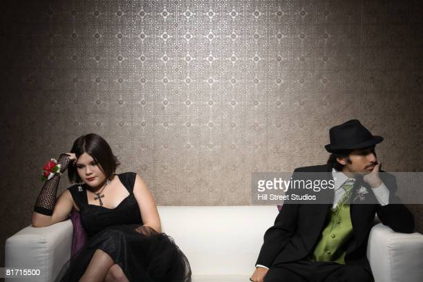 Multi-ethnic teenaged couple sitting on sofa