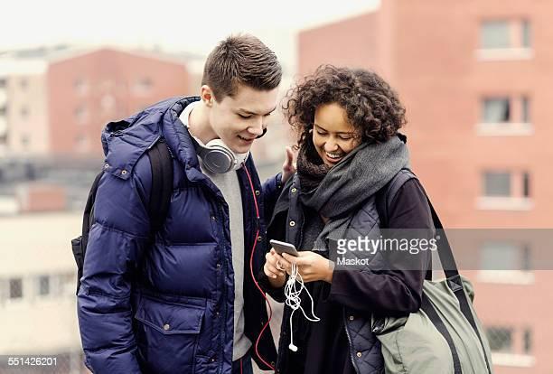 Multi-ethnic university students listening music through mobile phone against buildings
