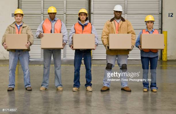 Multi-ethnic warehouse workers holding boxes