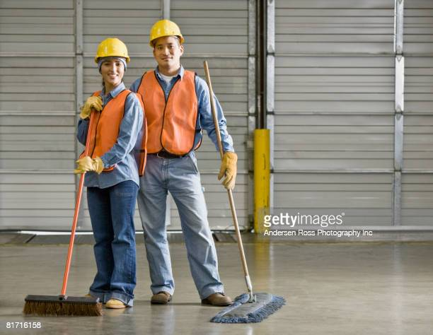 multi-ethnic warehouse workers holding brooms - janitor stock photos and pictures