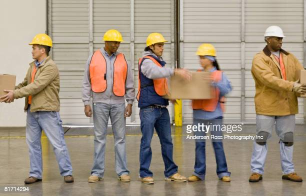 Multi-ethnic warehouse workers passing boxes
