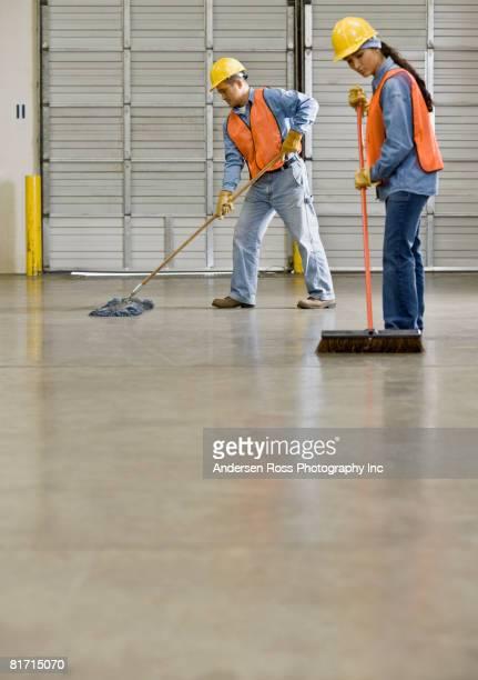 Multi-ethnic warehouse workers sweeping floor