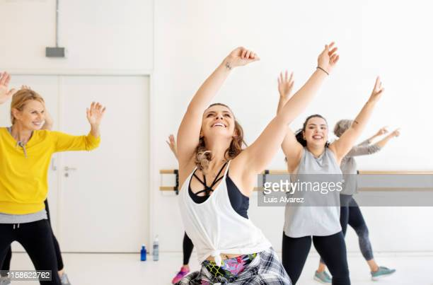 multi-ethnic women are dancing together at health club - fat lady in leggings stock photos and pictures