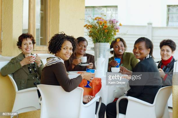 Multi-ethnic women having coffee outdoors