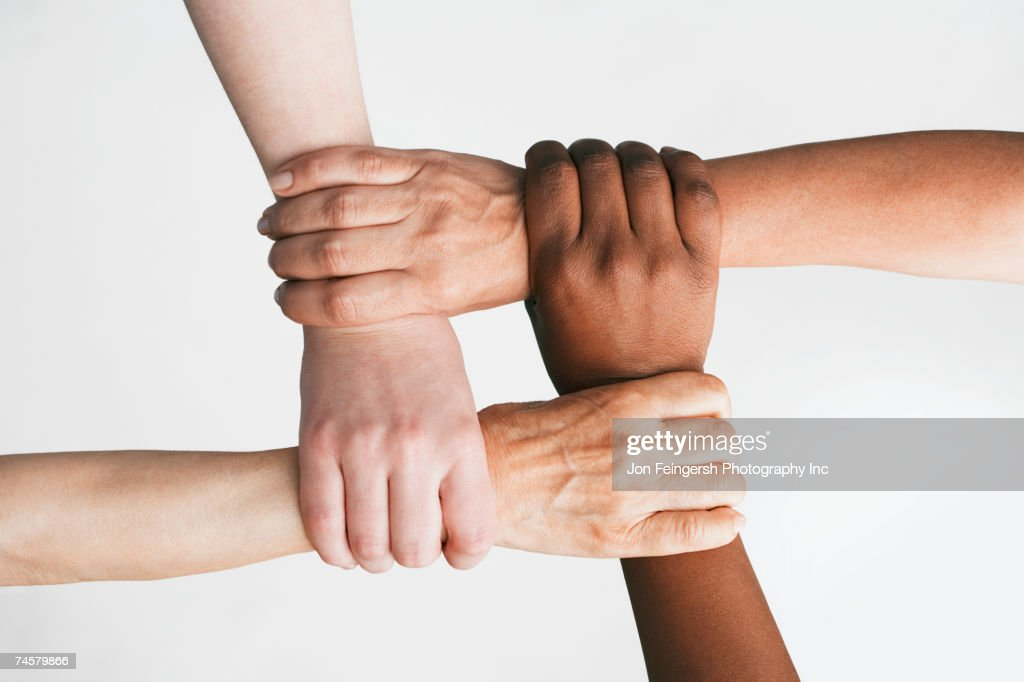 Multi-ethnic women holding wrists : Stock Photo