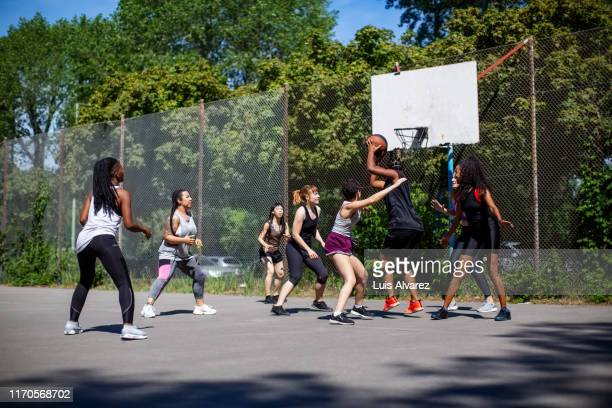 multi-ethnic women playing streetball at outdoor court - basketball sport stock pictures, royalty-free photos & images