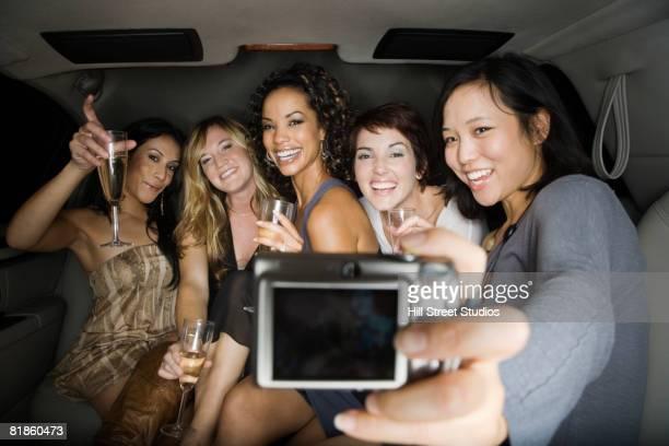 Multi-ethnic women taking own photograph