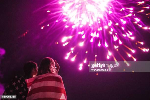 Multi-ethnic women taking photos of fireworks display in night sky