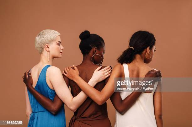 multi-ethnic women with arm around standing against brown background - arm around stock pictures, royalty-free photos & images