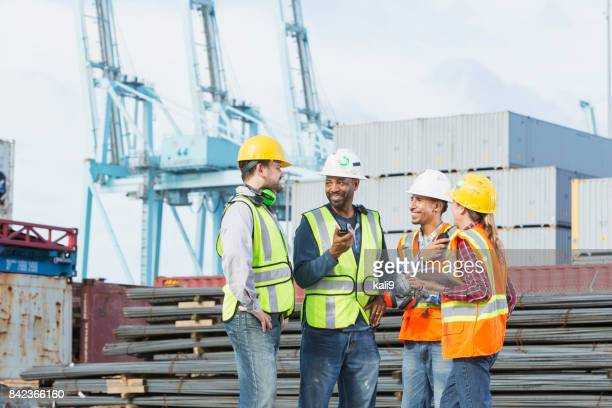 multi-ethnic workers at shipping port having a meeting - dock worker stock photos and pictures