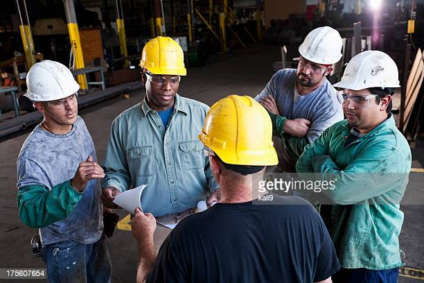 Multi-ethnic workers in fabrication shop