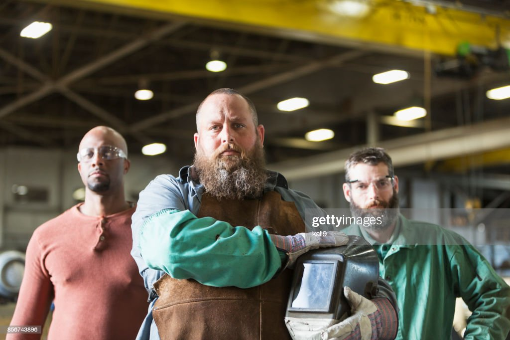 Multi-ethnic workers in metal fabrication plant : Stock Photo