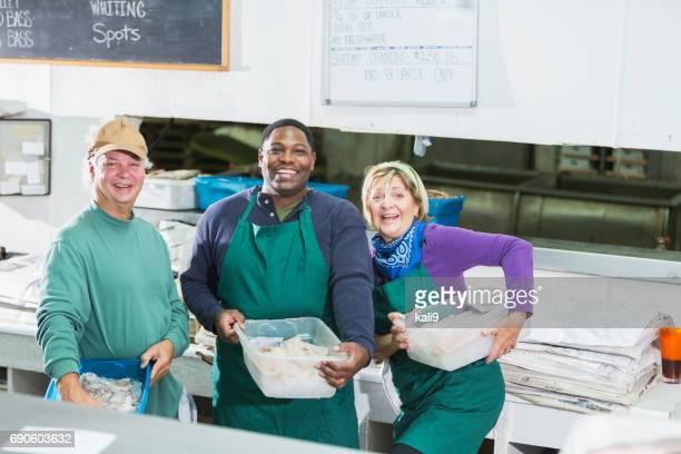 Travailleurs et multiethniques dans le magasin de fruits de mer