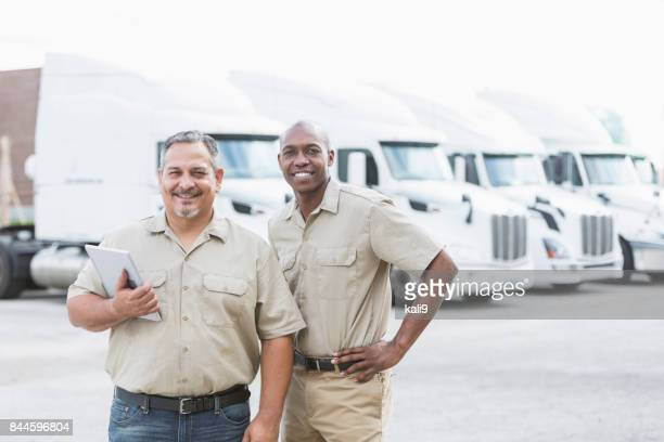Multi-ethnic workers standing in front of semi-trucks