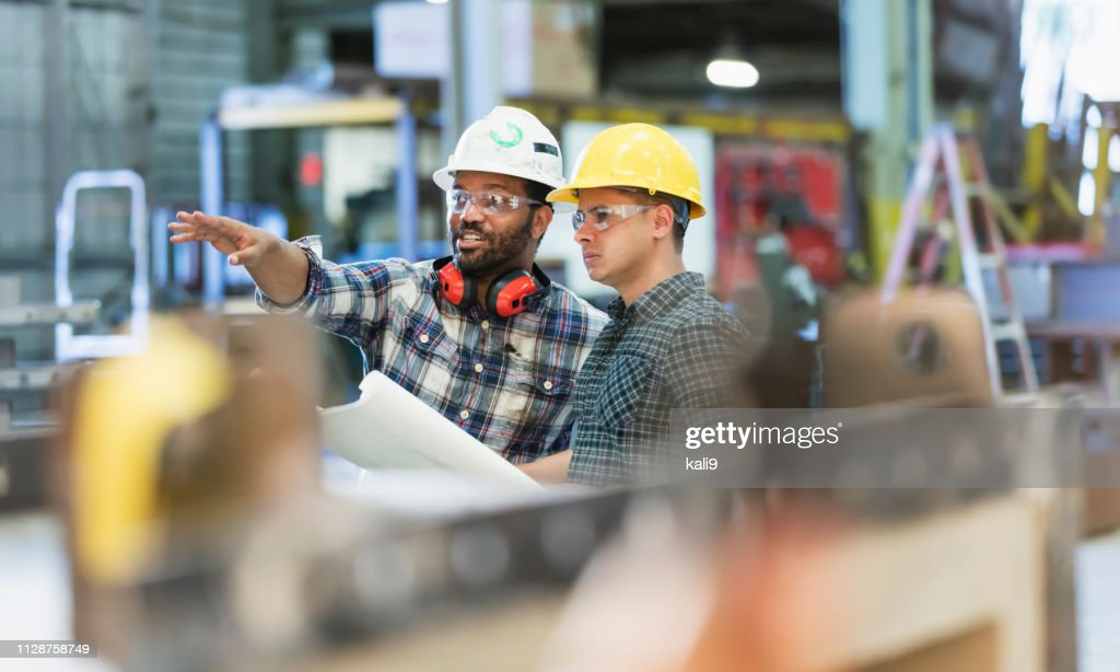 Trabajadores multiétnicos hablando en planta de fabricación de metal : Foto de stock