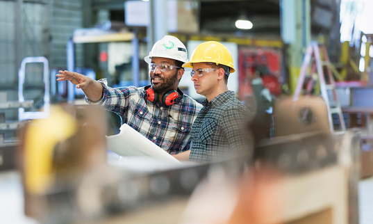 Multi-ethnic workers talking in metal fabrication plant 1128758749
