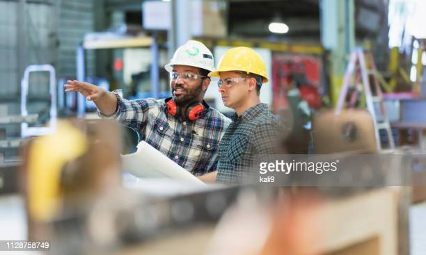 multi-ethnic workers talking in metal fabrication plant - construction industry stock pictures, royalty-free photos & images